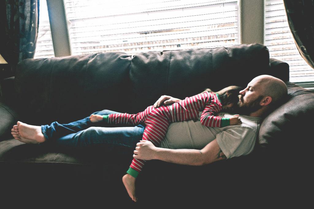 un papá durmiendo en el sillón con su pequeña encima