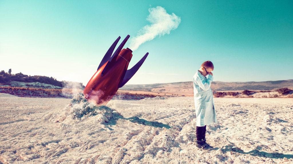 un niño con bata de médico en medio de un desierto y con un cohete estrellado en el suelo