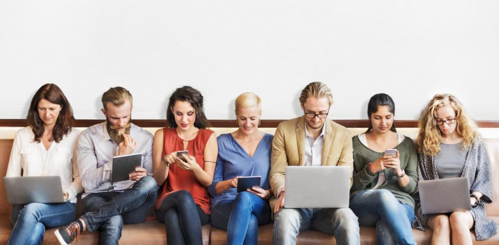 personas sentadas mirando sus dispositivos