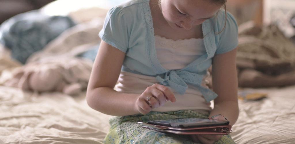 niña sentada mirando un tablet